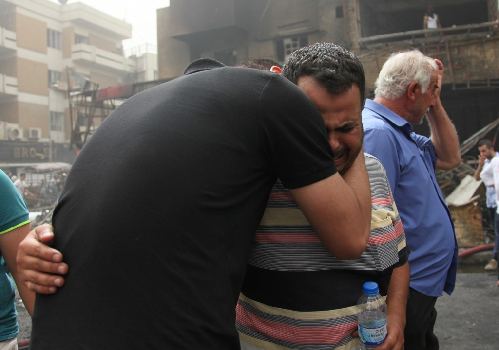 BAGHDAD, IRAQ - JULY 03: Iraqi people who lost their relatives mourn after a suicide car bombing, claimed by the terrorist organization DAESH, in the Karrada neighborhood of Baghdad, Iraq on July 03, 2016. It is reported that 60 people were killed and 100 wounded in the blast. ( Amir Saadi - Anadolu Agency )