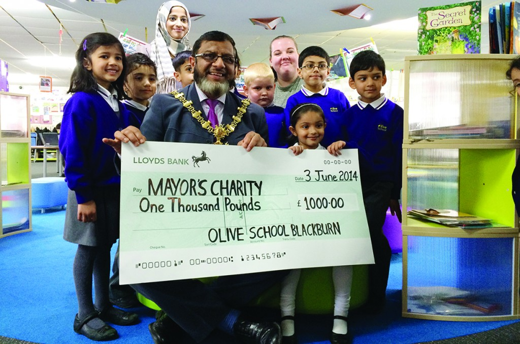 Children from the Olive Primary School present Blackburn Mayor Salim Mulla with a cheque for £1000 on June 3